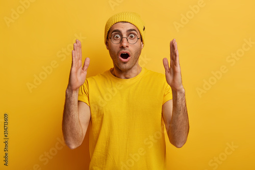 Obraz Stunned emotive man stretches hands and shows something huge, demonstrates large big size, tells about ammount, has shocked expression, dressed in casual wear, isolated over yellow background - fototapety do salonu
