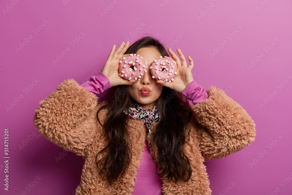 Fototapeta Photo of millennial girl keeps two glazed donuts on eyes, has lips folded, enjoys eating delicious sweet desserts, gets pleasure from sugary nutrition, wears warm coat, isolated over lilac background