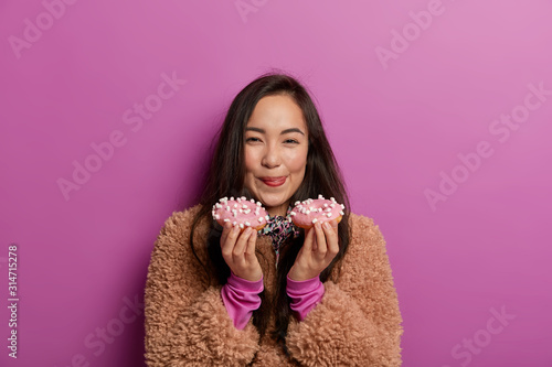 Photo Lovely woman licks lips with tongue, holds two donuts, has good appetite, enjoys