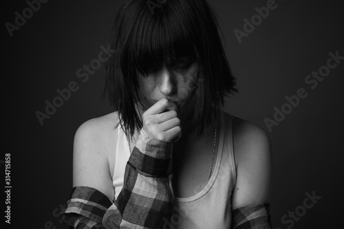 Leinwand Poster Crying young woman in studio. Black and white