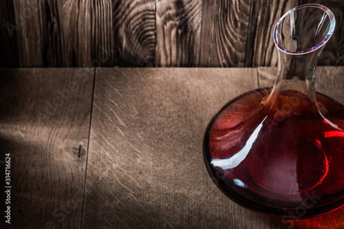 Photo decanter with red wine on wooden background