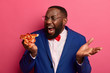 canvas print picture - Hungry black man bites very big piece of pizza, has appetite, wears formal clothing and spectacles poses against pink background, enjoys eating fast food in office, isolated on pink background.