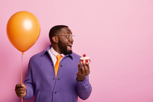 Cheerful Shocked Afro American Man Stands With Party Balloon And Sweet Dessert, Cannot Believe Eyes To See Former Lover On Birthday Dressed Elegantly Has Pleasant Wonder. Student Celebrates Graduation