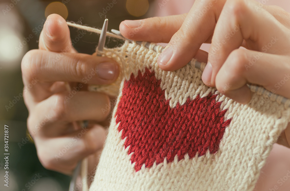 Fototapeta Concept of love and concern. Woman knitting the red heart for her loved one. Valentines postcard.