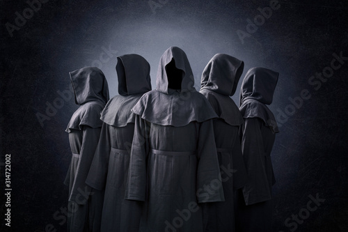 Photo Group of five scary figures in hooded cloaks in the dark