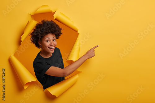 African American woman in black t shirt, stands in paper hole, points away on blank space, stands in ripped paper, has cheerful expression, isolated over yellow background. Advertising concept