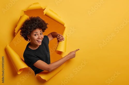 Pleased dark skinned Afro American woman stands in ripped background, laughs happily, poses in paper hole, points on right side, isolated on yellow wall Wallpaper Mural