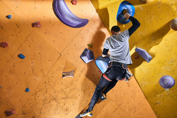 Rare view of powerful physically challenged man climbing yellow wall with colorful holds and artificial rocks of different shapes and sizes in bouldering gym. Full length shot, low angle view.