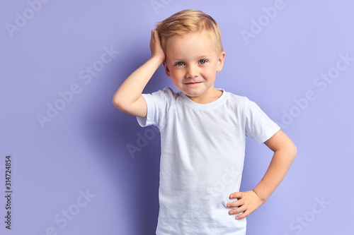 Obraz Honey little boy posing isolated over purple background, looking at camera. Portrait - fototapety do salonu