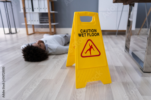 Obraz Man Falling On Wet Floor In Front Of Caution Sign - fototapety do salonu