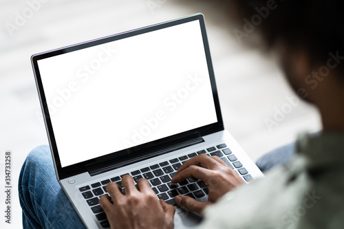 Obraz Young Man Using Laptop At Home - fototapety do salonu