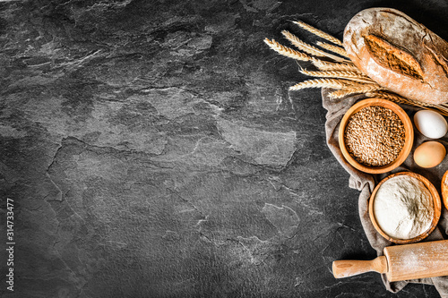 Fototapeta Fresh bakery food, rustic crusty loaves of bread and buns on black stone background. Top view and copy space for text. obraz