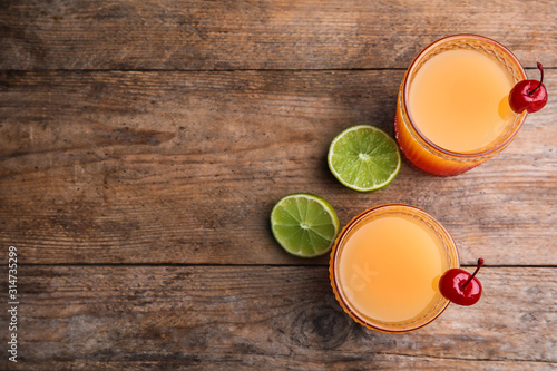 Fotografía  Fresh alcoholic Tequila Sunrise cocktails on wooden table, flat lay