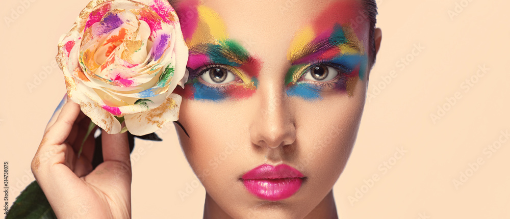 Fototapeta Beautiful girl model with multi-colored paints on her face. Woman with rose flower and bright color make-up. Cosmetics, beauty and makeup.  Spring and summer flowering  shopping - obraz na płótnie