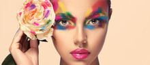 Beautiful Girl Model With Multi-colored Paints On Her Face. Woman With Rose Flower And Bright Color Make-up. Cosmetics, Beauty And Makeup.  Spring And Summer Flowering  Shopping