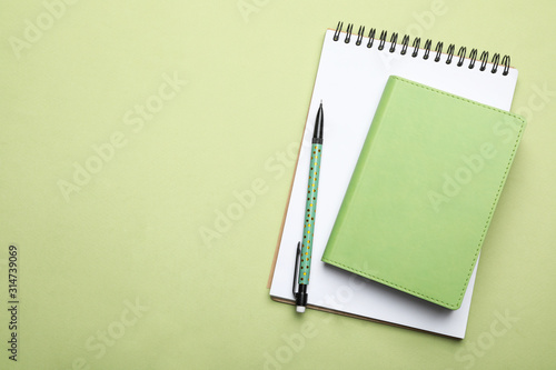 Obraz Stylish notebooks and pencil on light green background, top view. Space for text - fototapety do salonu