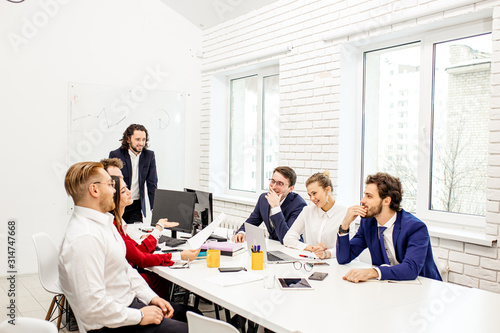 Fototapeta young caucasian people gathered in office to discuss business projects and ideas, wearing formal wear isolated in modern office. diverse enthusiastic people in boardroom obraz