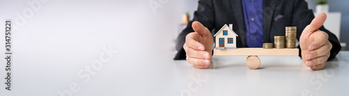 Fototapeta Businessperson Protecting House Model And Stacked Coins obraz