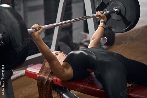 Professional female athlete dressed in black sportswear, lying on red bench, try Canvas Print
