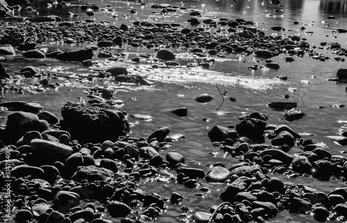 Fototapeta Corriente de agua rodeada de piedras, río con poca agua obraz