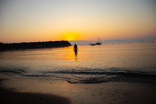 A Young Woman In The Sea And The View Of Sunrise