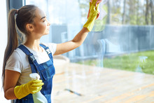 Young Caucasian Girl In Uniform, On Her Hands Yellow Protective Rubber Gloves. Spraying Detergent On Glass And Wiping Window With Pink Rag. Cleaning Service Concept