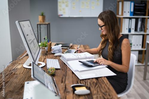 Accountant Calculating Tax At Desk Wallpaper Mural