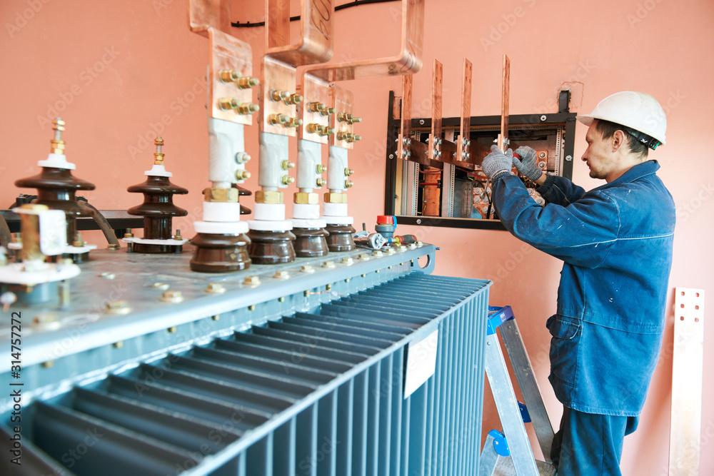 Fototapeta Electrician lineman worker installing power industrial transformer