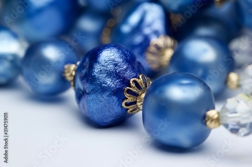 Macro abstract view of a vibrant blue and gold vintage costume jewelry necklace on a white background with copy space