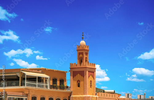 View of biggest tower on Jemaa EL Fnaa main city square. It is a beautiful sunny day at market place in Marrakesh's medina
