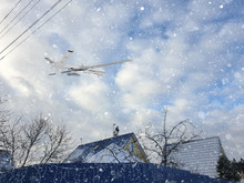 Automatic Drone Piloted Remotely By Radio Control Patrols Country Village Covered With Falling Snow