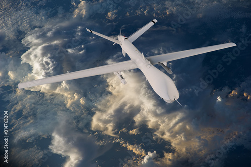 military RC military drone flies flies against backdrop of beautiful clouds on blue sky background Fototapet
