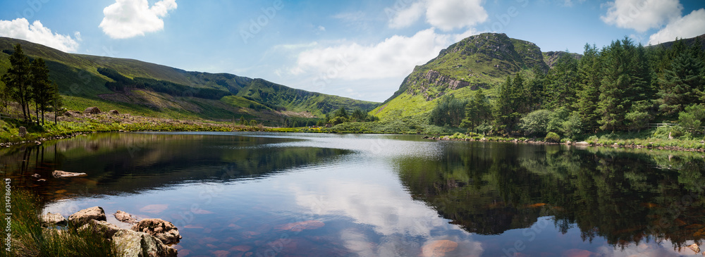 Fototapeta Scenic lake and mountains reflection of glentanassig woods in the Dingle Peninsula, County Kerry, Ireland