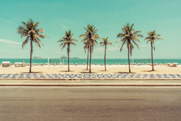 Sunny day with Palm Trees on Ipanema Beach in Rio De Janeiro, Brazil. Famous mosaic walkway in front of the beach