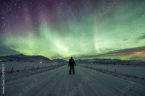 Northern Lights (Aurora Borealis) above a solo traveller on the road Wallpaper Mural