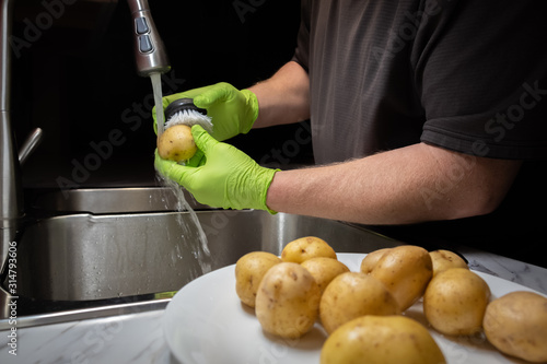 Fototapeta Washing and rinsing potatoes in preparation for cooking. Model wearing green disposable rubber gloves. obraz