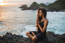 Young Woman Praying And Meditating Alone At Sunset With Beautiful Ocean And Mountain View. Self-analysis And Soul-searching. Spiritual And Emotional Concept