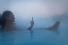 Young Female Tourist On Phone In Blue Lagoon Geothermal Spa In Iceland