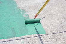 Hand Painting A Green Floor With A Paint Roller For Waterproofing