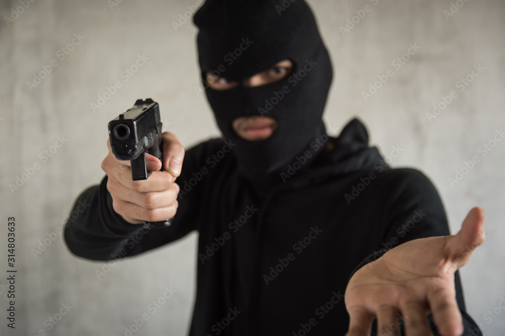 Fototapeta Robber with gun aiming into people