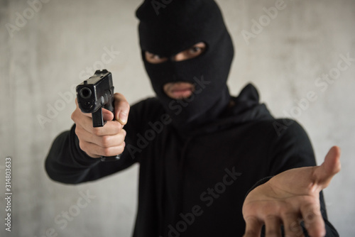 Stampa su Tela Robber with gun aiming into people