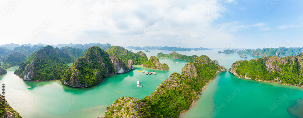 Fototapeta Aerial view of Ha Long Bay Cat Ba island, unique limestone rock islands and karst formation peaks in the sea, famous tourism destination in Vietnam. Scenic blue sky.