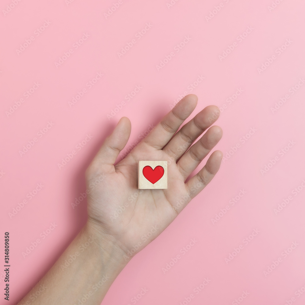 Fototapeta Hands holding Wood cube with  red heart on pink background.