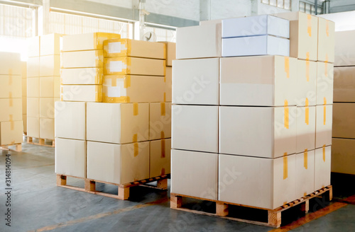 Fototapeta Stack of package boxes on wooden pallet, cargo shipment in industry warehouse obraz