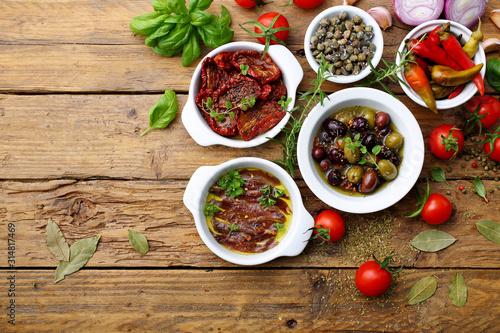 Photo cibo mediterraneo spunti con acciughe pomodori secchi olive sfondo rustico
