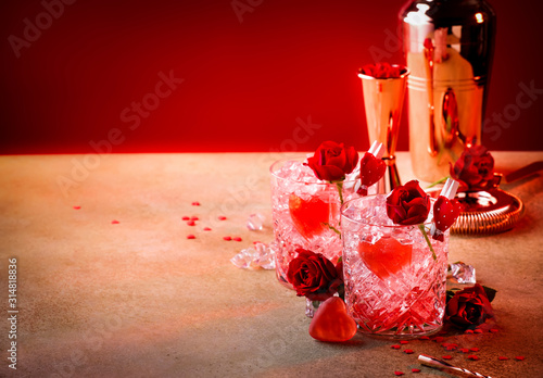 Obraz Roses julep Valentine's day cocktail with red roses and hearts on a festive background - fototapety do salonu