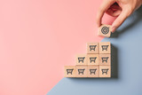 Sale volume increase make business success, Hand holding wood cube with icon goal and shopping cart symbol.
