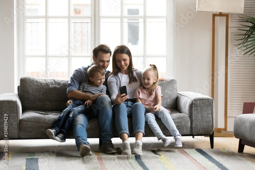 Fototapeta Happy parents with kids relax at home using cellphone obraz