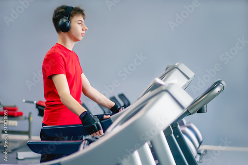 young man in sportswear in the gym on a treadmill Wallpaper Mural