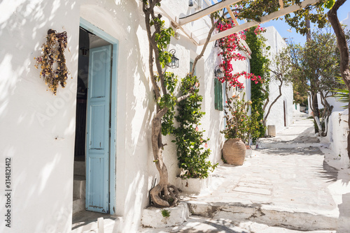 Beautiful traditional greek street with flowers on Amorgos island, Greece.